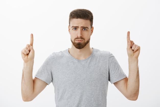 Портрет несчастного, грустного и глупого красивого мужчины с бородой и усами, хмурящегося и мрачно улыбающегося, указывая вверх, выражая сожаление или ревность, недовольно стоящего у серой стены Бесплатные Фотографии