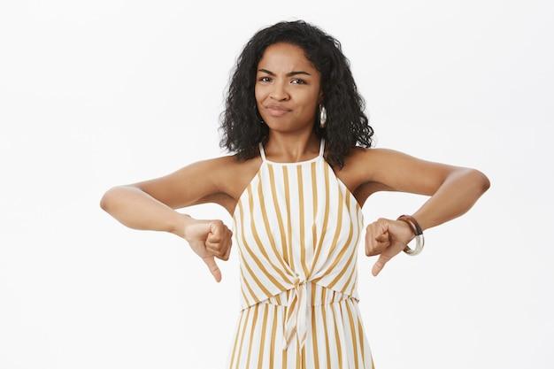 Портрет неудовлетворенной, неудовлетворенной властной темнокожей женщины с кудрявой прической в желтом стильном комбинезоне, ухмыляющейся и показывающей палец вниз Бесплатные Фотографии