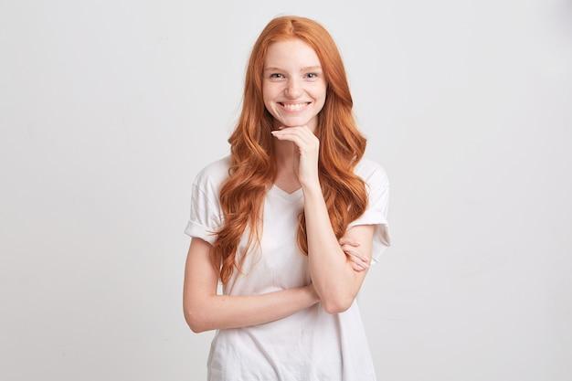 赤い波状の長い髪とそばかすがtシャツを着ている動揺して落ち込んでいる若い女性の肖像画は白い壁に孤立して心配と不幸を感じます 無料写真