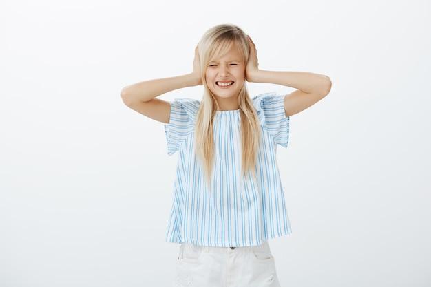 Портрет расстроенной сытой молодой девушки со светлыми волосами, гримасничающей от неприязни, закрывающей уши ладонями, отвлеченной и раздраженной громким шумом с улицы Бесплатные Фотографии