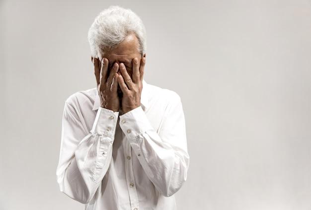 泣きながら顔を覆っている動揺した老人の肖像画。灰色の壁に分離 無料写真