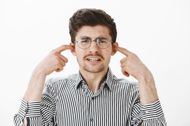 Портрет расстроенного ноющего обычного парня в круглых очках и полосатой рубашке, закрывающего уши указательными пальцами, с недовольным выражением лица, испытывающего неприязнь, слыша ужасную царапину на доске Бесплатные Фотографии