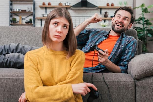Портрет расстроен молодой женщины, сидя возле улыбающегося молодого человека, аплодисменты во время игры в видеоигры Бесплатные Фотографии