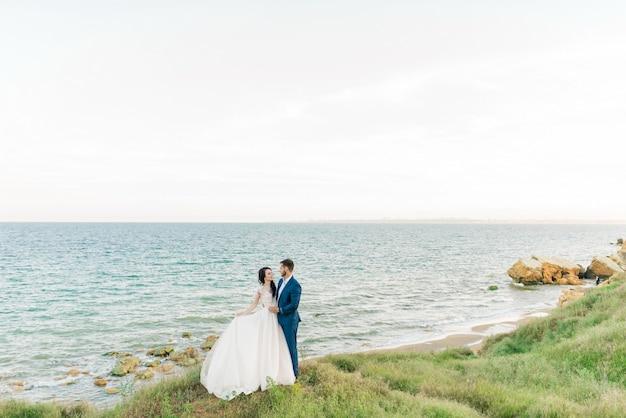古い大聖堂でポーズをとる花束と結婚式の若い新郎新婦の肖像画。結婚式の日にキスする新婚旅行のカップル、恋に幸せなカップル、結婚式のキス Premium写真