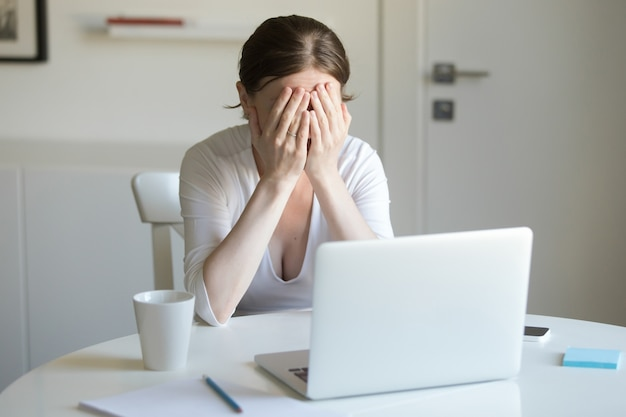Portrait of woman at the desk with laptop, hands closing face Free Photo