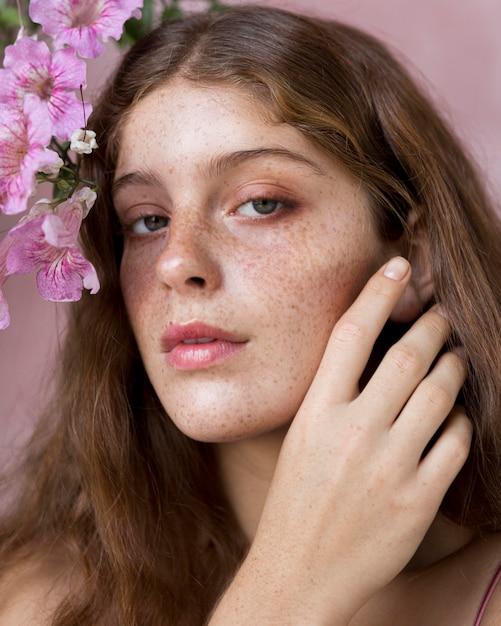彼女の顔にピンクの花を保持している女性の肖像画 無料写真
