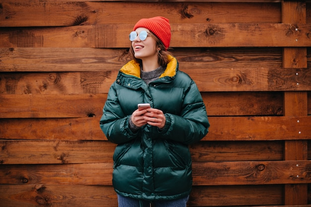 Портрет женщины в изумрудно-зеленом пальто на деревянной стене Бесплатные Фотографии