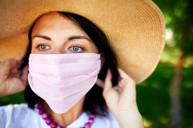 麦わら帽子をかぶった女性の肖像画は、ピンクの保護マスクを脱いで、街の屋外公園で、コンセプトセルフケア、コロナウイルスパンデミック中の生活、検疫を超えて、 Premium写真