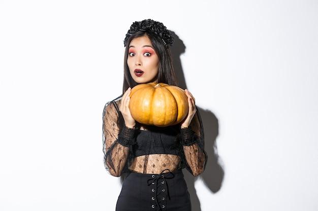 Портрет женщины, поднимающей тяжелую тыкву, готовясь к хэллоуину Бесплатные Фотографии