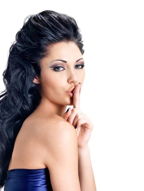 静かな表情の女性の肖像画。唇の近くに指を持つブルネットの少女の写真、沈黙の概念 無料写真