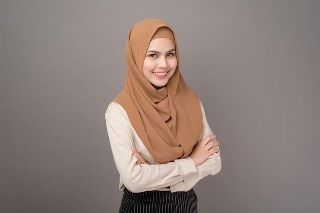 Портрет женщины с хиджабом улыбается на сером Premium Фотографии