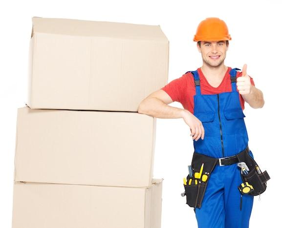 白い背景で隔離の親指アップサインを示す紙の箱を持つ労働者配達人の肖像画 無料写真