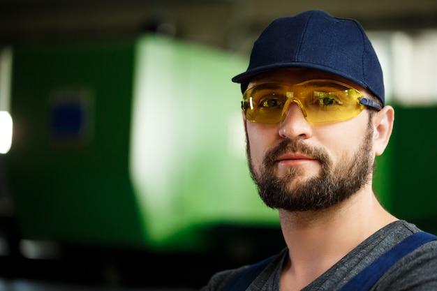 Портрет работника в спецодежде, стальной фон фабрики. Бесплатные Фотографии