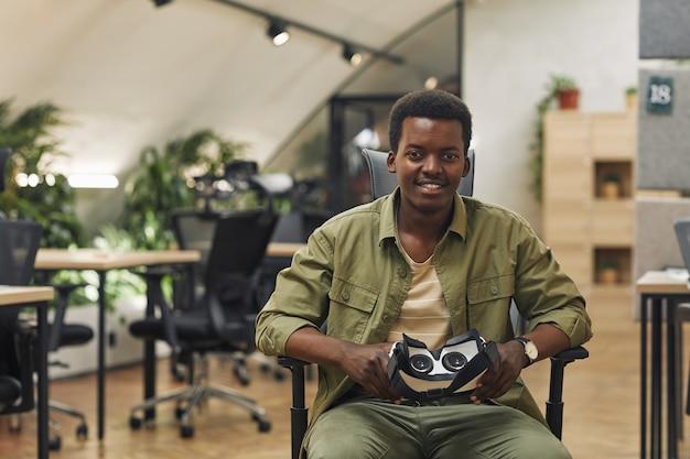 Vr 장비를 들고 현대 사무실에 앉아 카메라에 웃고 젊은 아프리카 계 미국인 남자의 초상화 공간 복사 프리미엄 사진