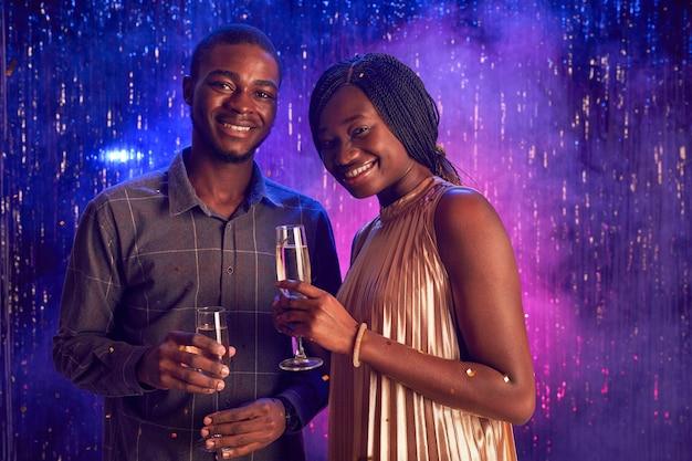 ナイトクラブ、コピースペースでパーティーを楽しみながらシャンパングラスを持ってカメラに笑顔の若いアフリカ系アメリカ人カップルの肖像画 Premium写真
