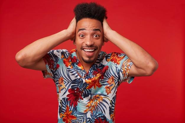 Портрет молодого афроамериканца в гавайской рубашке, выглядит удивленным и счастливым, стоит на красном фоне и держит голову. Бесплатные Фотографии