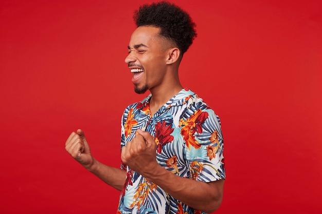 Портрет молодого афроамериканца в гавайской рубашке, выглядит счастливым и радостным, стоит на красном фоне, сжимает кулаки и радуется победе. Бесплатные Фотографии