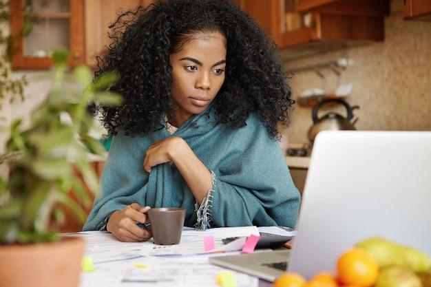 Портрет молодой африканской женщины пьет чай, глядя на экран ноутбука с целенаправленным выражением лица Бесплатные Фотографии