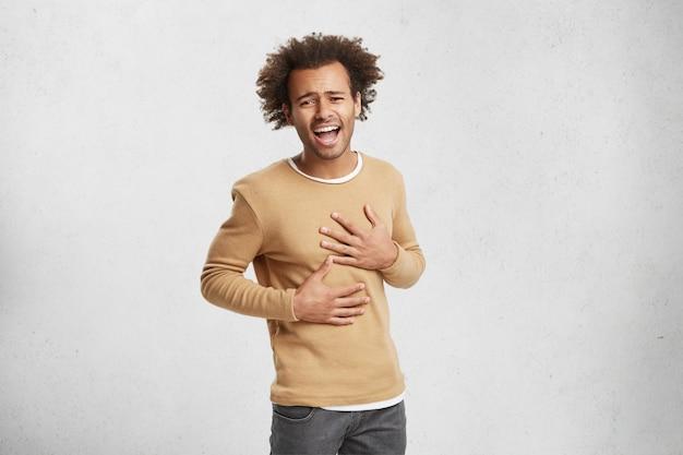 若いアフロアメリカンの男の肖像は笑いをやめることができない、胃に手を保つ 無料写真