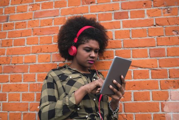 赤いヘッドフォンを屋外で彼女のデジタルタブレットを使用して若いアフロアメリカンの女性の肖像画。技術コンセプト。 無料写真