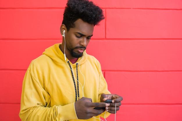 Портрет молодого афро-человека, использующего свой мобильный телефон с наушниками у красной стены. концепция технологии и образа жизни. Premium Фотографии