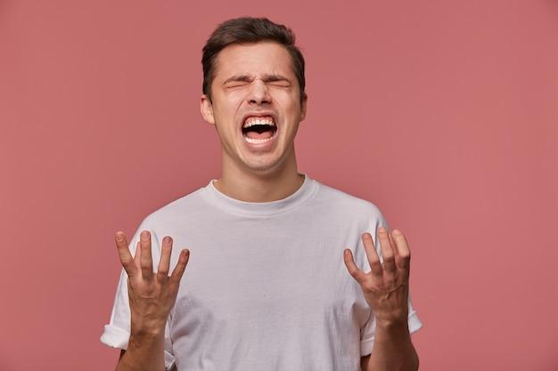 Портрет молодого сердитого парня в пустой футболке, слышит плохие новости и выглядит злым, стоит на розовом и кричит с несчастным выражением лица. Бесплатные Фотографии
