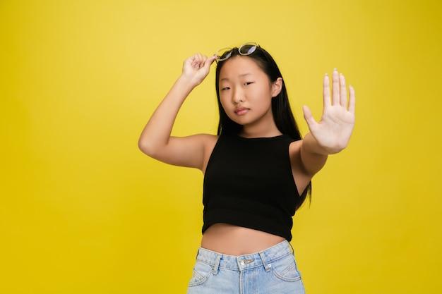 黄色のスタジオで隔離の若いアジアの女の子の肖像画 無料写真
