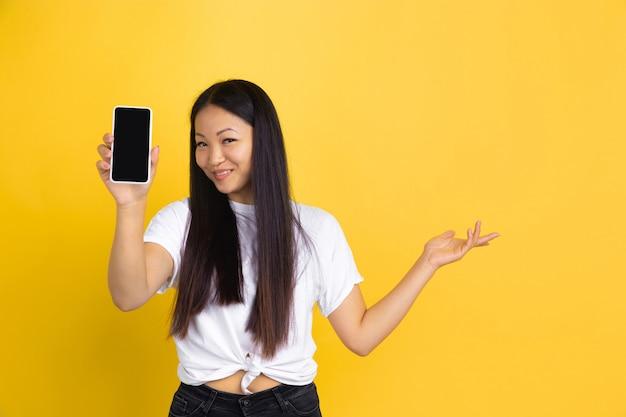 Портрет молодой азиатской женщины, изолированные на желтой стене Бесплатные Фотографии