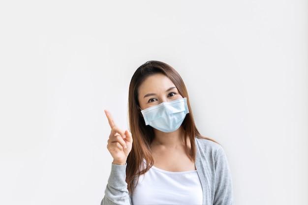 人差し指を上に向けて保護マスクを身に着けている若いアジアの女性の肖像画 Premium写真