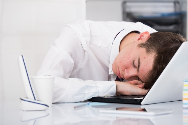 Portrait of young assistant sleeping in the office Free Photo