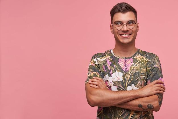 꽃이 만발한 셔츠에 젊은 매력적인 쾌활한 남자의 초상화, 행복, 복사 공간과 광범위하게 웃고 분홍색 배경 위에 의미합니다. 무료 사진