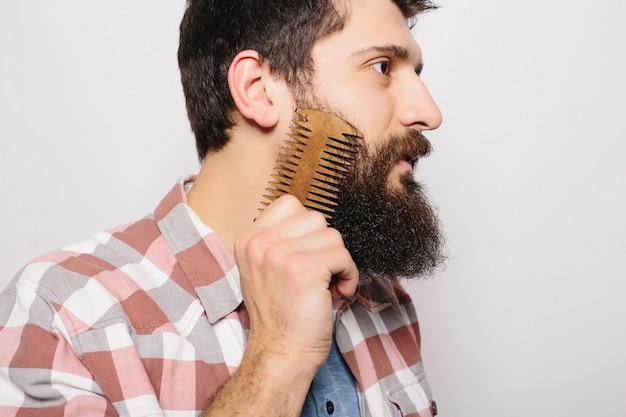 나무 빗을 들고 그의 두꺼운 수염을 하 고 심각 하 고 자신감 표정으로 젊은 매력적인 빨간 머리 Hipster 남성의 초상화. 살롱에서 빗질 체크 무늬 셔츠에 세련된 수염 이발사. 수평 무료 사진
