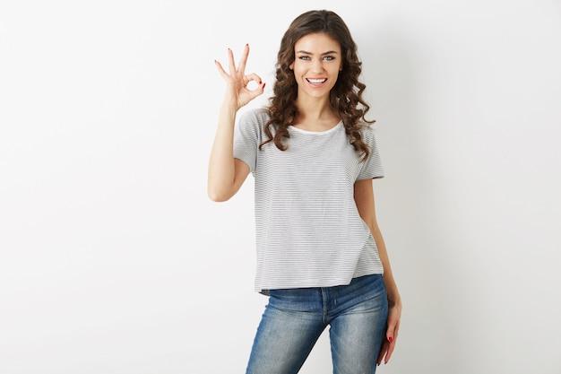 カジュアルな服を着た若い魅力的な女性の肖像tシャツとジーンズ、肯定的なジェスチャー、笑顔、幸せ、流行に敏感なスタイル、分離、巻き毛、大丈夫サイン、陽気な気分、美しい顔を見せて 無料写真