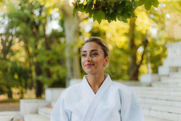 Портрет молодой привлекательной женщины в белом кимоно. спорт женщина на открытом воздухе. боевые искусства Premium Фотографии