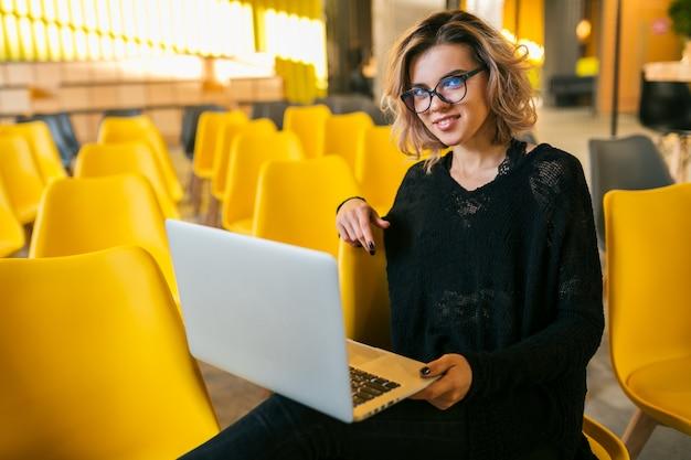 講堂に座っている若い魅力的な女性の肖像画、ラップトップに取り組んで、眼鏡、教室、多くの黄色い椅子、オンラインの学生教育、フリーランサー、スタイリッシュ 無料写真