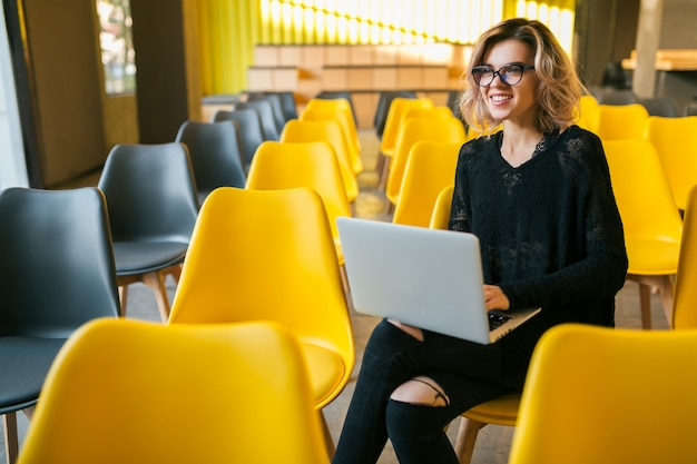 講堂に座っている、ラップトップに取り組んで、眼鏡をかけている、多くの黄色い椅子のある教室、学生の学習、オンライン教育、フリーランサー、幸せ、笑顔の若い魅力的な女性の肖像画 無料写真
