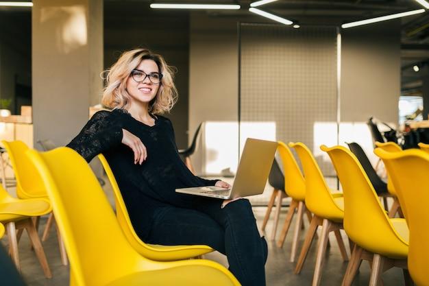 Портрет молодой привлекательной женщины сидя в лекционном зале работая на стеклах компьтер-книжки нося, студент учя в классе с много желтых стулов Бесплатные Фотографии