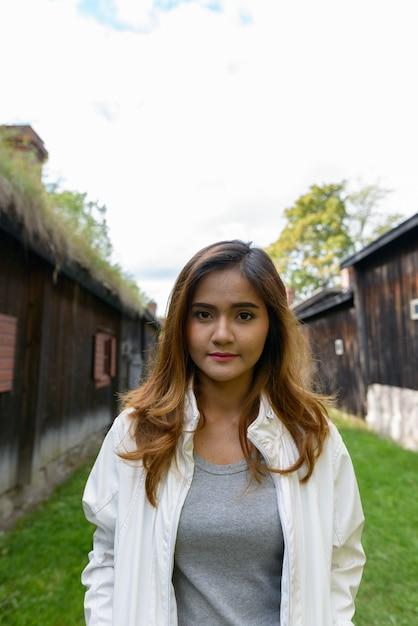 Портрет молодой красивой азиатской женщины посреди выровненных старых деревянных коттеджей Premium Фотографии