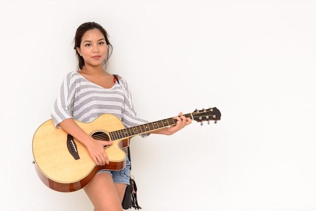 屋外で隔離のギターを弾く若い美しいアジアの女性の肖像画 Premium写真