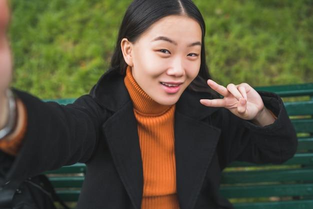 屋外の公園のベンチに座って、selfieを取る若い美しいアジアの女性の肖像画。 Premium写真
