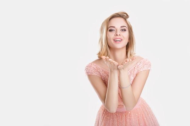 Портрет молодой красивой белокурой чувственной женщины в розовом коктейльном платье, целующейся на сером фоне Premium Фотографии