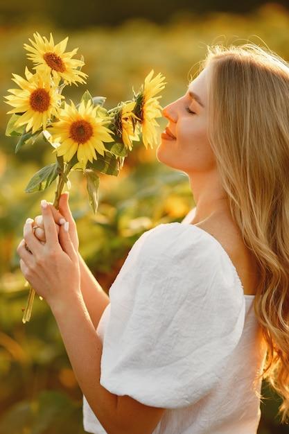 バックライトのひまわり畑で若い美しいブロンドの女性の肖像画。夏の田舎のコンセプト。女性とひまわり。夏の光。屋外の美しさ。 無料写真
