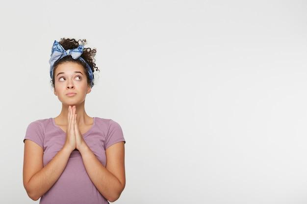 祈り、祈りのコンセプトで折り畳まれた若い美しいブルネットの女性の肖像画 無料写真