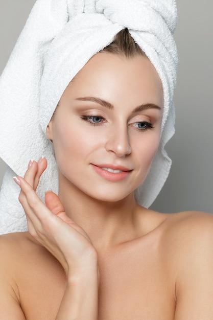 흰색 배경 위에 절연 그녀의 얼굴을 만지고 젊은 아름 다운 백인 여자의 초상화. 프리미엄 사진