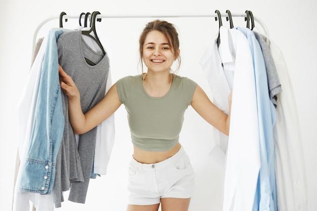 白い壁にカメラを見て笑顔のハンガーワードローブを探している若い美しい幸せな女性の肖像画。 無料写真