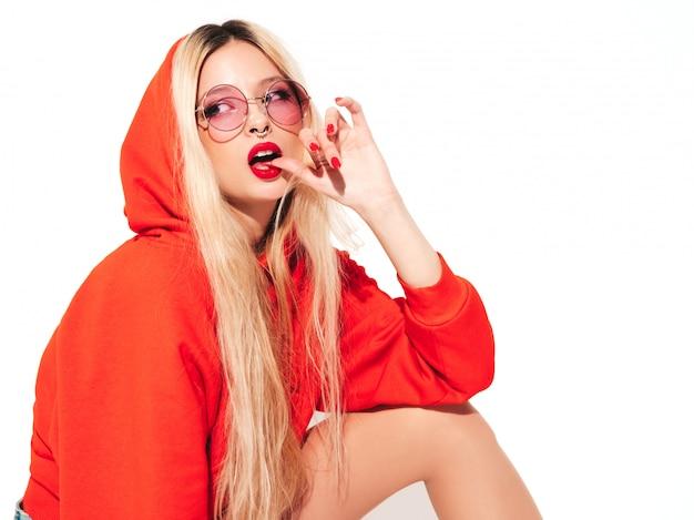 Портрет молодой красивой битник плохая девушка в модном красном балахоне и серьги в носу. позитивная модель с удовольствием. кусает палец Бесплатные Фотографии