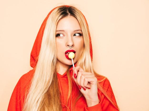 トレンディな赤いパーカーと彼女の鼻にイヤリングの若い美しい流行に敏感な悪い女の子の肖像画。丸い砂糖菓子を舐める肯定的なモデル 無料写真
