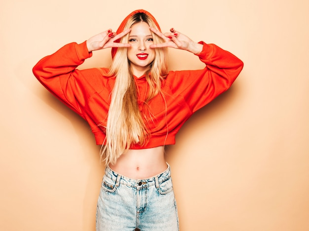 Портрет молодой красивой битник плохая девушка в модном красном балахоне и серьги в носу. позитивная модель показывает знак мира Бесплатные Фотографии