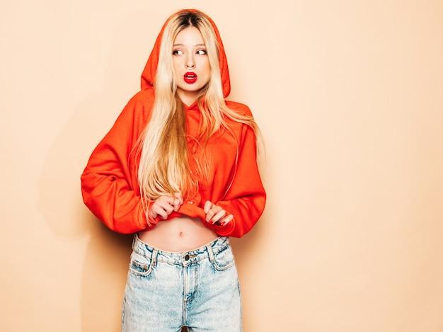 Портрет молодой красивой битник плохая девушка в модном красном балахоне и серьги в носу. позитивная модель Бесплатные Фотографии