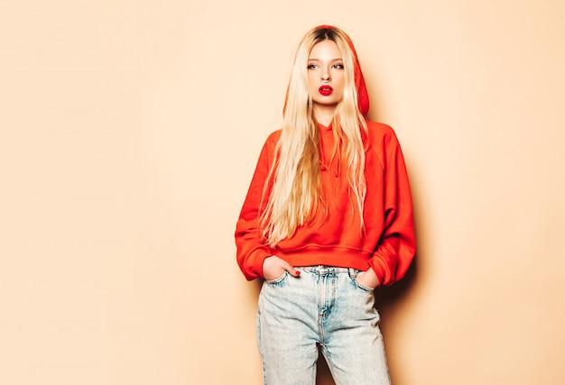 Портрет молодой красивой битник плохая девушка в модном красном балахоне и серьги в носу. сексуальная беззаботная блондинка позирует в студии. Бесплатные Фотографии